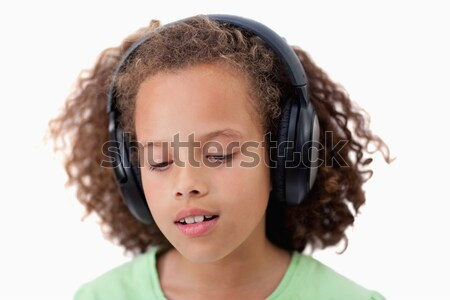 Calm girl listening to music against a white background Stock photo © wavebreak_media