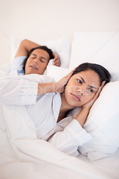 Young woman covering her ears to block her boyfriends snoring Stock photo © wavebreak_media