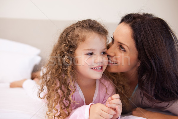 Young mother whispering into her daughters ear Stock photo © wavebreak_media