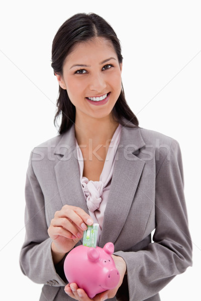 Smiling businesswoman putting money into piggy bank against a white background Stock photo © wavebreak_media