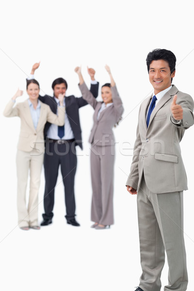 Salesman giving thumb up while getting celebrated against a white background Stock photo © wavebreak_media
