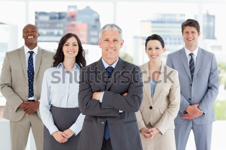 Sorridere squadra di affari piedi mani fianchi ufficio Foto d'archivio © wavebreak_media