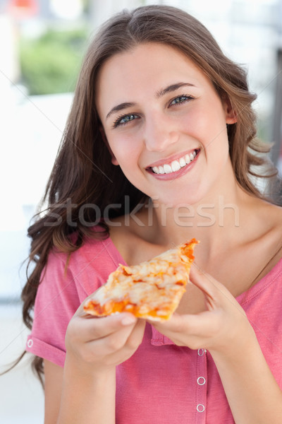 A close up shot of a woman looking into the camera as she holds a piece of pizza in her hand Stock photo © wavebreak_media
