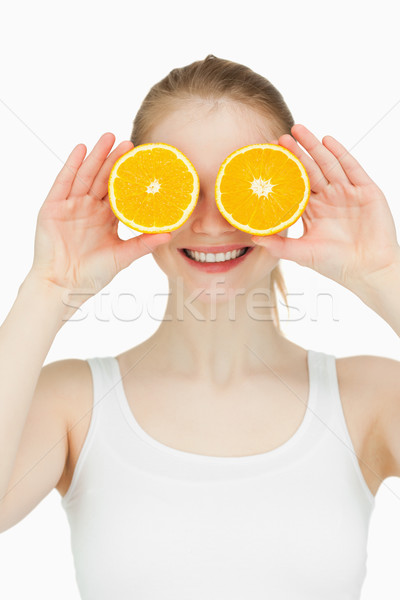 Cheerful woman placing oranges on her eyes against white background Stock photo © wavebreak_media