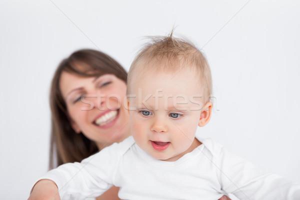 Happy mother holding her cute baby Stock photo © wavebreak_media