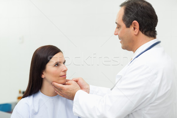 Doctor auscultating the neck of a patient in an examination room Stock photo © wavebreak_media