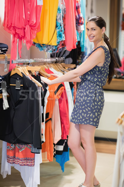 Woman is standing at a clothes rack smiling in the shop Stock photo © wavebreak_media
