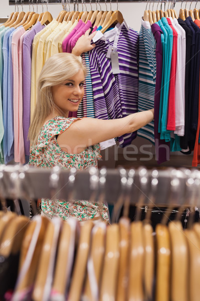 Stock photo: Woman standing by the clothes rack of a boutique smiling
