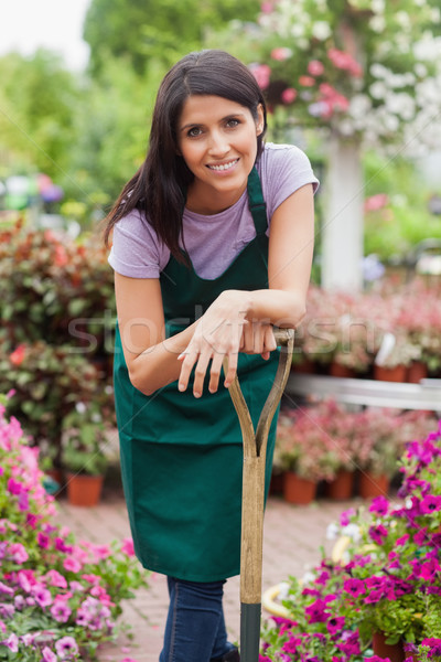 Woman working in garden center smiling while leaning on spade Stock photo © wavebreak_media