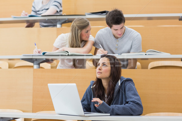 Students sitting at the lecture hall while girl thinking at laptop  Stock photo © wavebreak_media