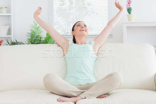 Carefree woman sitting on the couch in the living room while stretching Stock photo © wavebreak_media