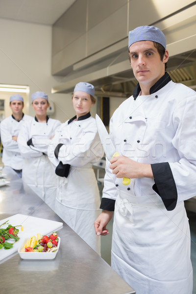 Chef looking stern holding a knife with team behind him Stock photo © wavebreak_media