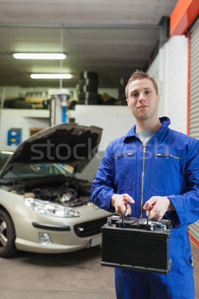 Confident auto mechanic with car battery Stock photo © wavebreak_media