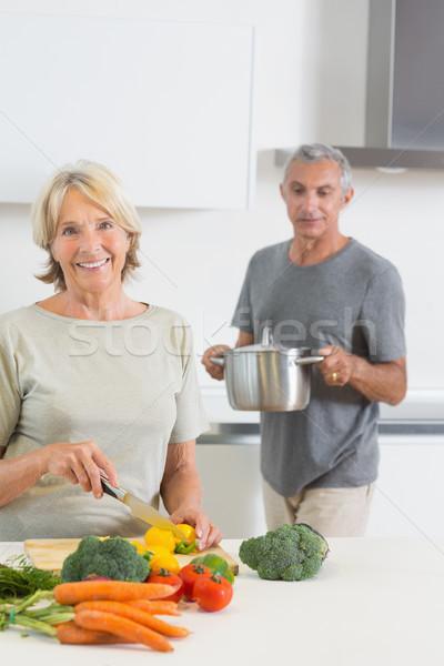 Husband bringing a pan to his smiling wife Stock photo © wavebreak_media