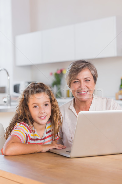 Smiling child and granny looking at the camera with laptop Stock photo © wavebreak_media
