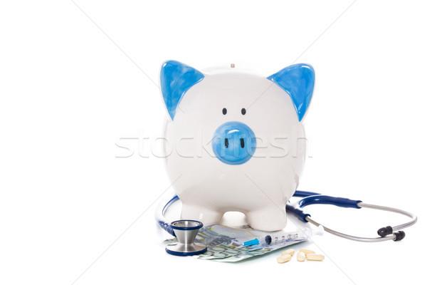 Piggy bank sitting on euro notes with stethoscope syringe and pi Stock photo © wavebreak_media
