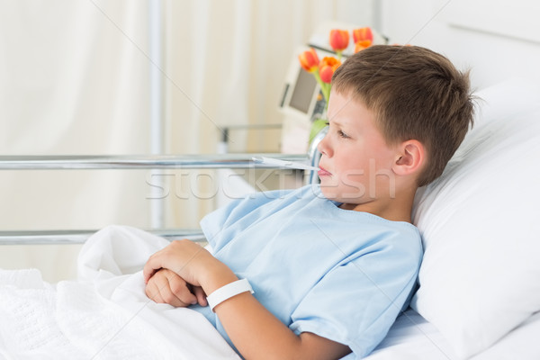 Boy in hospital with thermometer in mouth Stock photo © wavebreak_media