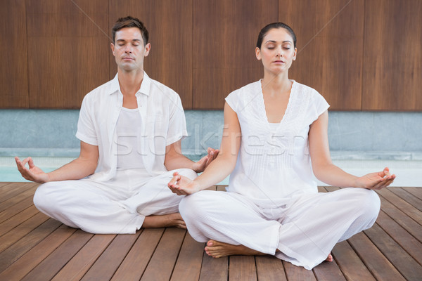 Attractive couple in white meditating in lotus pose Stock photo © wavebreak_media