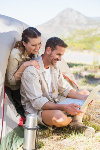 Outdoorsy couple looking at the laptop outside tent Stock photo © wavebreak_media