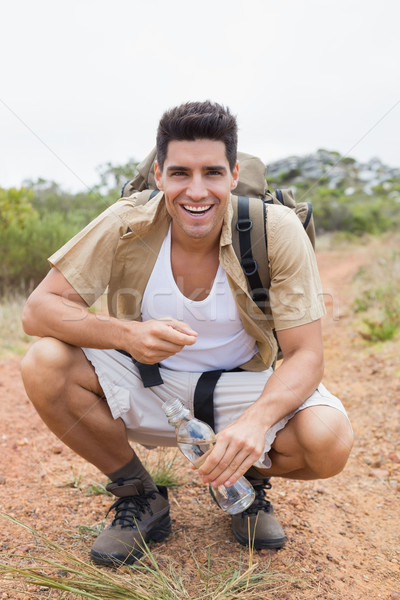 Cheerful hiking man crouching on mountain terrain Stock photo © wavebreak_media