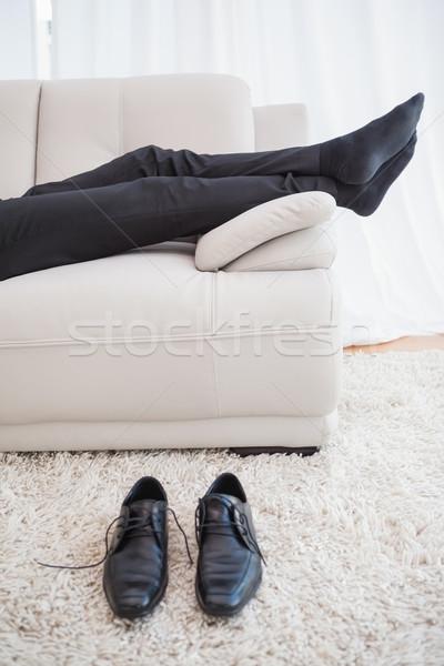 Empresário sofá pernas visível casa sala de estar Foto stock © wavebreak_media