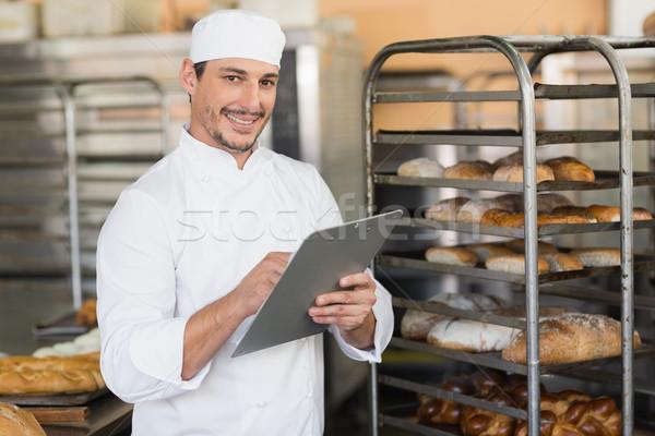 Smiling baker writing on clipboard Stock photo © wavebreak_media