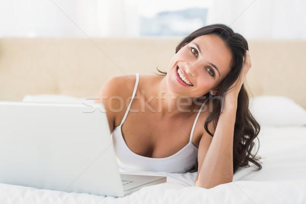 Stock photo: Happy brunette using her laptop