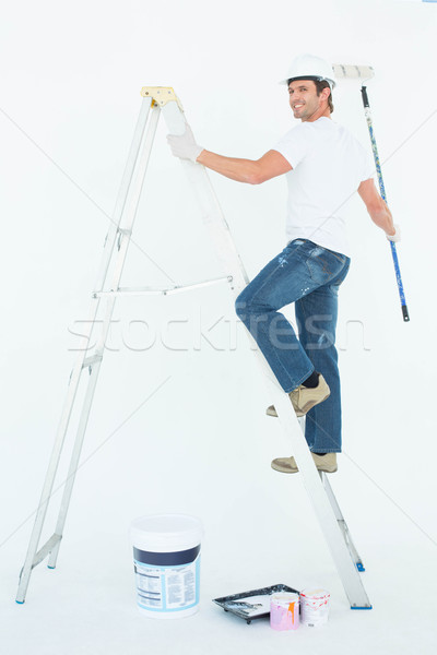 Happy man on ladder painting with roller Stock photo © wavebreak_media