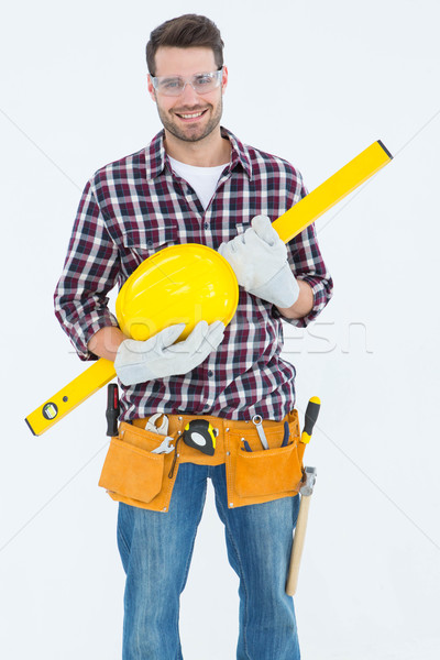Handyman holding hard hat and spirit level Stock photo © wavebreak_media