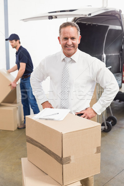 Smiling manager standing behind stack of cardboard boxes Stock photo © wavebreak_media