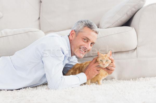 Happy man with dog lying on rug Stock photo © wavebreak_media