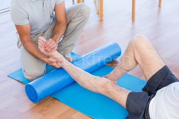 Trainer working with man on exercise mat  Stock photo © wavebreak_media