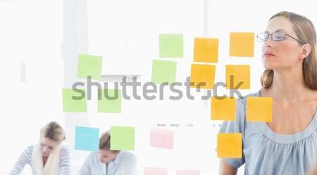 Glimlachend zakenvrouw schrijven sticky notes venster kantoor Stockfoto © wavebreak_media
