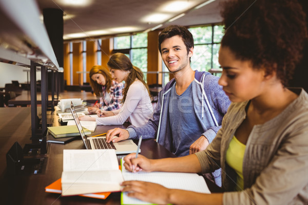 Student looking at camera while studying with classmates Stock photo © wavebreak_media