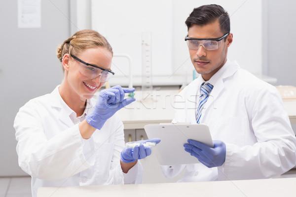Scientists looking at petri dish and taking notes  Stock photo © wavebreak_media