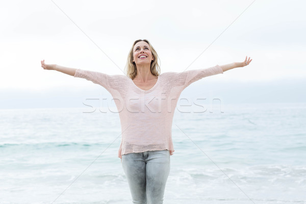 Smiling pretty blonde standing by the sea arms outstretched Stock photo © wavebreak_media
