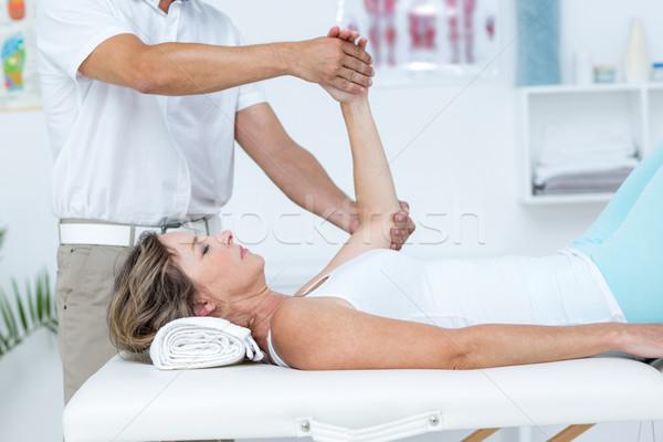 Doctor bending his patient arm Stock photo © wavebreak_media