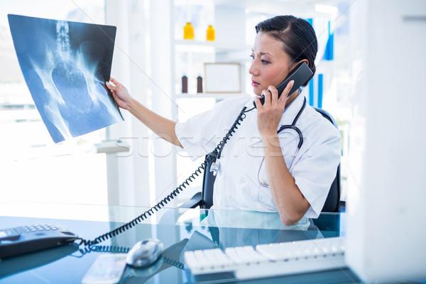 Doktor bakıyor telefon görüşmesi tıbbi ofis kadın Stok fotoğraf © wavebreak_media