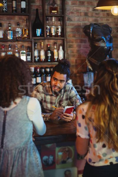 Barman toma para bloc de notas contra pub Foto stock © wavebreak_media