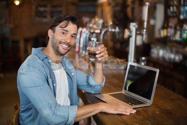 Young man holding beer while sitting by laptop in pub Stock photo © wavebreak_media