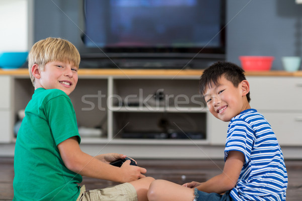 Happy siblings playing video games in living room Stock photo © wavebreak_media