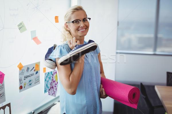 Portrait of smiling executive holding exercise mat and shoes Stock photo © wavebreak_media