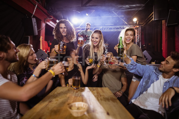 Cheerful friends toasting drink at table with performer singing on stage  Stock photo © wavebreak_media
