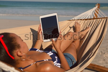Man using digital tablet while relaxing in hammock Stock photo © wavebreak_media