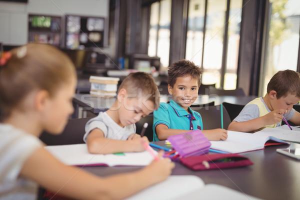 Foto stock: Sorridente · lição · de · casa · biblioteca · escolas · lápis