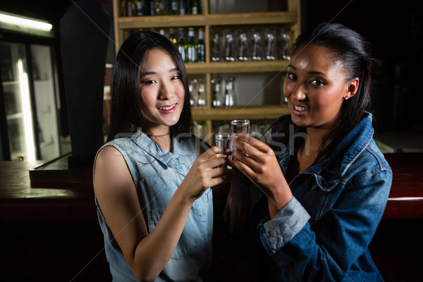 Female friends toasting tequila shot glasses Stock photo © wavebreak_media
