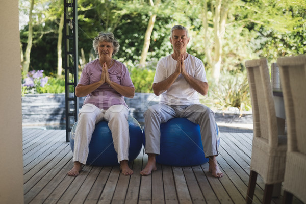 Full length of senior couple meditating together while sitting at porch Stock photo © wavebreak_media