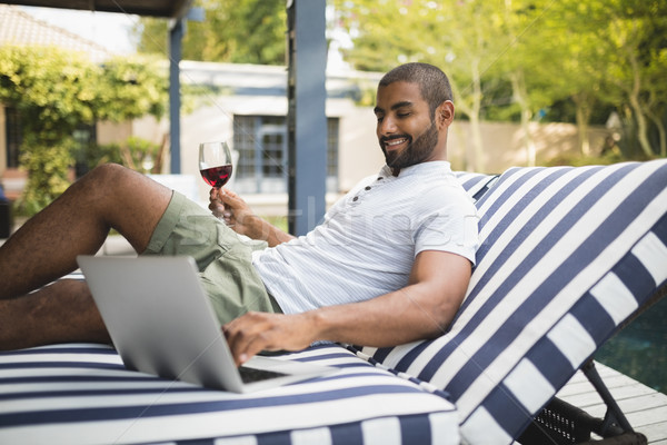 Man holding wineglass while using laptop on lounge chair Stock photo © wavebreak_media