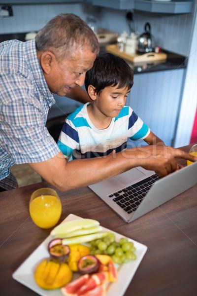 Nonno nipote utilizzando il computer portatile cucina home tecnologia Foto d'archivio © wavebreak_media