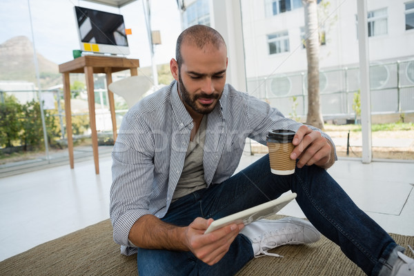 Designer holding disposable cup using tablet computer while sitting on floor Stock photo © wavebreak_media